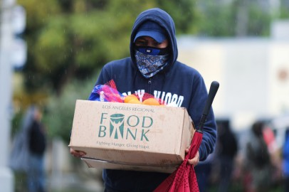 A man carries away fresh food at a Los Angeles Regional Food Bank giveaway