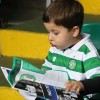 A young Celtic fan reads the match programme prior to the UEFA Champions League group C match between Celtic FC and VfL Borussia Moenchengladbach at Celtic Park on October 19, 2016 in Glasgow,Scotland