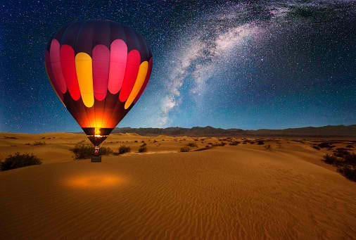 A majestic hot air balloon soars under the stars of the Milky Way, over the desert - Mesquite Dunes of Death Valley National Park.
