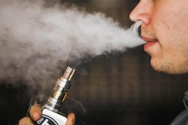 A teenage man using a flavored e-cigarette
