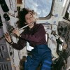 Candid view of Mission Specialist Ellen Ochoa, in the aft flight deck, playing a flute.