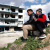 Migrants sit outside an abandoned building next to the main bus terminal in the border city of Edirne