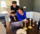 Cheryl Noah and Alex Barkin use a computer during a family Passover Seder to connect with relatives who are unable to gather together due to the outbreak of Coronavirus disease (COVID-19) in Maplewood, New Jersey, U.S