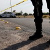 A policeman keeps watch near the wreckage of a car that was burnt in a blockade set by members of the Santa Rosa de Lima Cartel to repel security forces during a police operation on the outskirts of Celaya