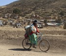 An indigenous woman cycles nears Cohana Bay on the shores of Titicaca lake, some 110 km (68 miles) northwest of La Paz