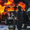 A police officer stands near a burning police vehicle after demonstrators set it on fire during a protest