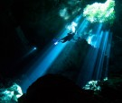 A scuba diver swims through rays of light coming into a massive underground, underwater cave in the Cenote Taj Maha in Quintana Roo, Mexico on September 27, 2018