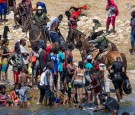 Border agents on horses with Haitian migrants