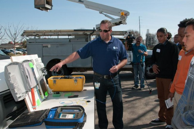 An AT&T technician shares a look at equipment with students involved in HACEMOS' annual High Tech Day